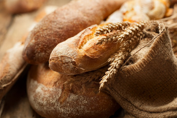 heap of various bread with ears of wheat on wooden background