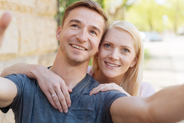 Outdoor selfie portrait of young cheerful couple