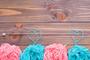 Tangles of pink and mint yarn,  hearts with needle on a wooden background. Top view