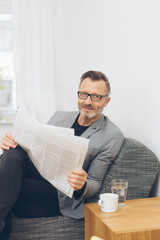 Mature man reading newspaper while sitting on sofa