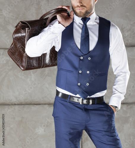 Part of travel business man. Blue suit vest, tie, leather