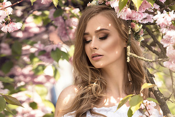 Attractive blonde girl in blooming garden.