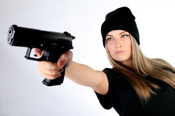 Beautiful girl with a gun imitates a robbery