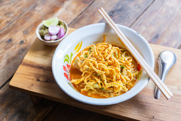 Curried noodle soup (Khao soi) with chicken meat and spicy coconut milk on wood table. Thai food cuisine northern style in Chiang Mai.