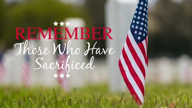 Small American flags and headstones at National cemetary- Memorial Day display - with copy
