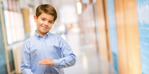 Handsome toddler child with green eyes holding something, size concept at school corridor