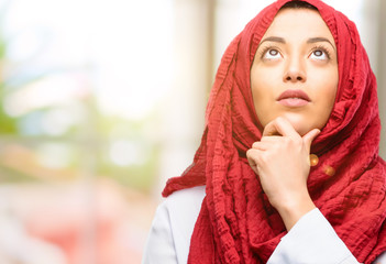 Young arab woman wearing hijab thinking and looking up expressing doubt and wonder