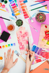 Flatlay with woman's hands holding brush, pallets, pencils, watercolors, colored paper and other stationary supplies, artist or designer workplace