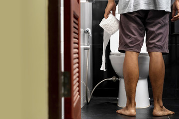 Man holding tissue roll in toilet of his house