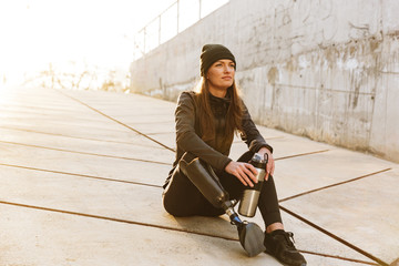 Photo of athletic disabled girl with prosthetic leg in sportswear, sitting on concrete floor outdoors and looking aside