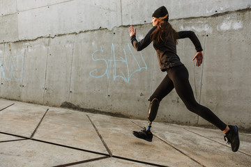 Portrait of disabled athlete woman with prosthetic leg in tracksuit, running outdoor along concrete wall