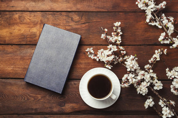 Sakura branches with flowers, White cup with Black Coffee and Book on a dark wooden background. Flat lay, top view