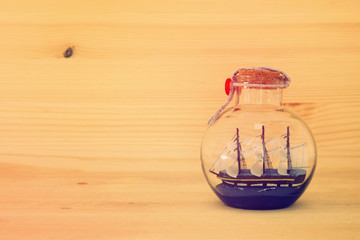 nautical concept image with sail boat in the bottle over wooden table. Selective focus.