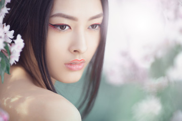 Gorgeous fantasy girl face close-up against nature beauty background. Perfect model with creative vivid makeup and pink lipstick on lips and traditional japanese hairstyle posing outside. Outdoor
