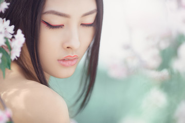Gorgeous fantasy girl face dreaming with closed eyes against nature beauty background. Perfect model with creative vivid makeup and pink lipstick on lips and traditional japanese hairstyle posing