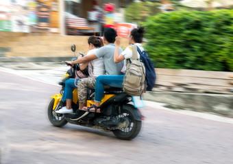 drei Personen auf einem Roller in Thailand, Asien.