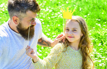 Dad and daughter sits on grass at grassplot, green background. Family spend leisure outdoors. Best friends concept. Child and father posing with crown and eyeglasses photo booth attributes.