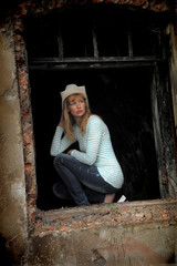 blond woman in cowboy hat sitting on the window of a ruined house
