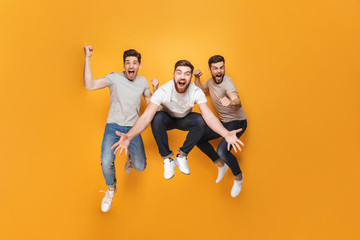 Three young excited men jumping together