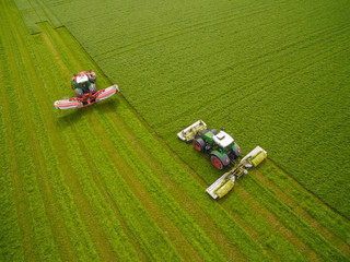 Aerial view of two tractor mowing a green fresh grass field,   farmer in a modern tractors mowing a green fresh grass field on a sunny day