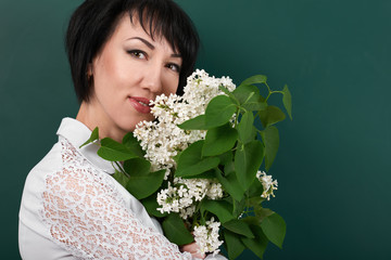 portrait of woman with lilac flowers on green blackboard background