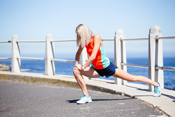 Beautiful blond female fitness athlete stretching before her outdoor run next to the ocean