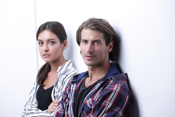 offended couple leaning on a white wall