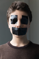 Boy with tape on the mouth and eyes