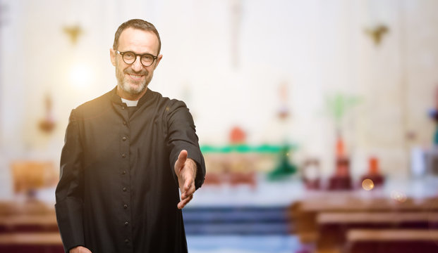 Priest religion man holds hands welcoming in handshake pose, expressing trust and success concept, greeting at church