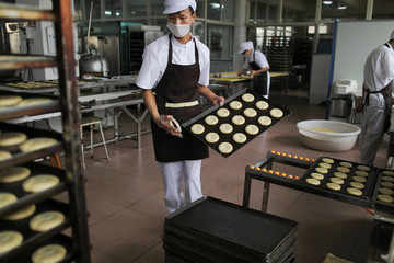 Worker holds a tray of rose pastries at a factory that makes flower pastries, in Kunming