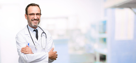 Doctor senior man, medical professional with crossed arms confident and happy with a big natural smile laughing at hospital