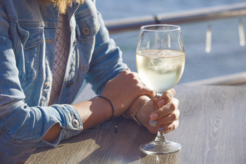female hand with glasses of white wine