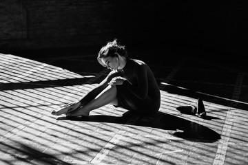 Sensual girl sitting on floor in sun rays