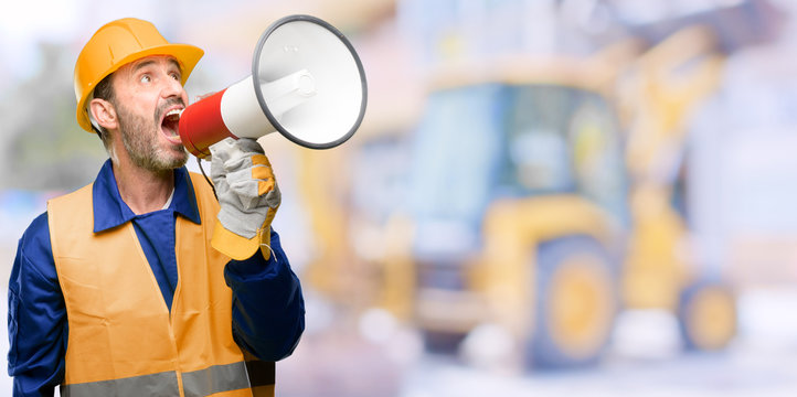 Senior engineer man, construction worker communicates shouting loud holding a megaphone, expressing success and positive concept, idea for marketing or sales at work