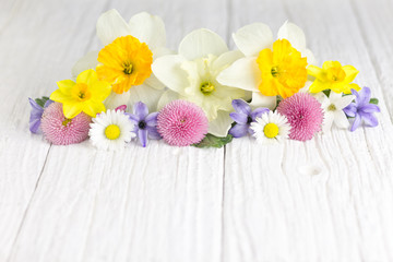 Colorful flowers centered on a white wooden table.