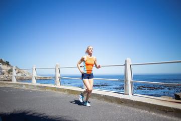 Beautiful blond female fitness athlete running outside near the ocean