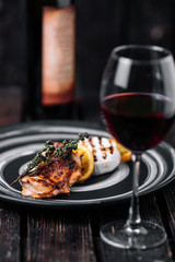 Baked Camembert with caramelized orange and grilled chicken on wood background.
