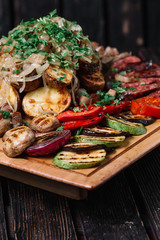Assorted delicious grilled vegetables and sausages on cutting bo