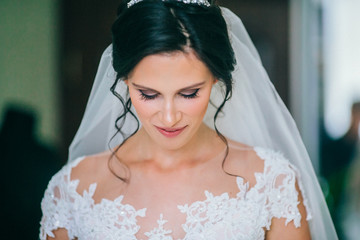 Attractive bride with style wedding hairstyle. Bride looking down. Woman before wedding ceremony.