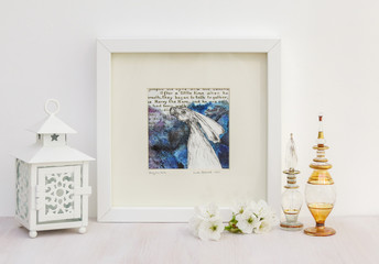 White interior display. Drawing of hare on a collaged blue background in frame. With egyptian glass scent bottles, tea light and cherry blossom.