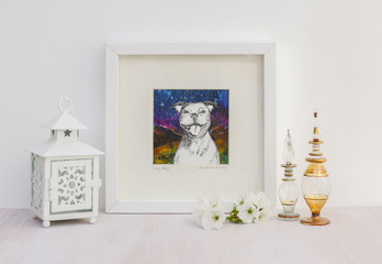 White interior display. Drawing of a happy Staffy dog with a big smile, on a collaged background in frame. With egyptian glass scent bottles, tea light and cherry blossom.