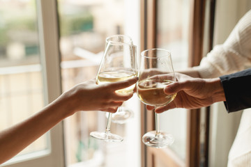 Young happy friends cheering with glasses of white wine, group of people celebrating anniversary at home, cozy atmosphere, family dinning at restaurant, togetherness and traditional concept
