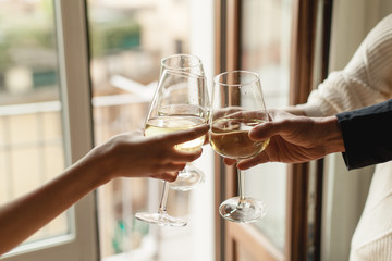 Young happy friends cheering with glasses of white wine, family dinning at home, enjoyment and party concept, best friends celebrating at home, traditional and holidays concept