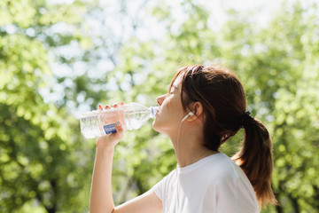 Young girl drinking clean water while having a run in the park and listening to music, concept of sport and healthy lifestyle, cropped image of hipster sporty runner girl drinking water