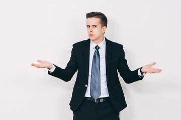 Young business man having a doubt. Closeup portrait of clueless young man in suit. Skeptic, unsure, uncertain, doubts concept.