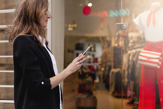 Young beautiful woman walking along the street using smartphone and doing online shopping, stylish girl looking at clothes shop window while browsing internet on her mobile phone and doing shopping
