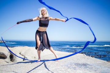 Beautiful female fitness model doing ribbon dancing on a granite rock overlooking the ocean on a bright and sunny summer day