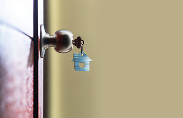 Open door with keys, House key in keyhole with small house