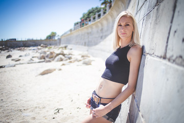 Sexy blond female model posing in denim shorts and crop top by the beach