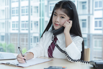 asian girl dreaming to be a business concept,businesswoman talking on office telephone.